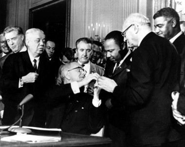 In this July 2, 1964, file photo, President Lyndon B. Johnson reaches to shake hands with Dr. Martin Luther King Jr. after presenting the civil rights leader with one of the 72 pens used to sign the Civil Rights Act in Washington. Surrounding the president, from left, are, Rep. Roland Libonati, D-Ill., Rep. Peter Rodino, D-N.J., Rev. King, Emanuel Celler, D-N.Y., and behind Celler is Whitney Young, executive director of the National Urban League. (AP file)