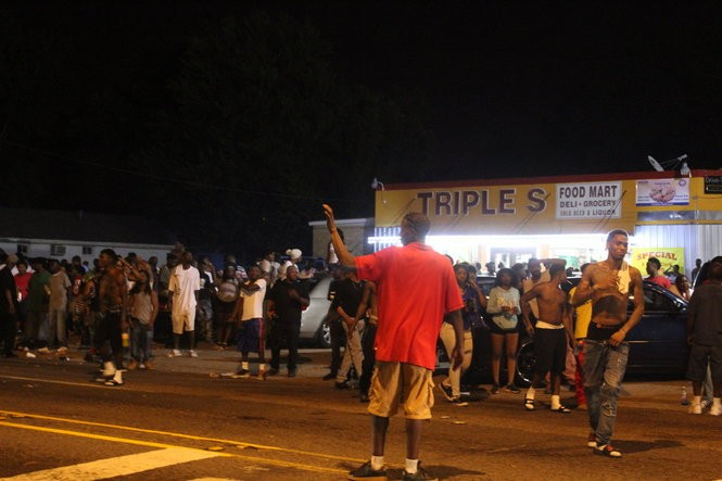 A man stops traffic outside Triple S Food Mart on North Foster Drive in Baton Rouge amid protests over the police-involved shooting of Alton Sterling. The protests continued well after midnight, according to news reports.