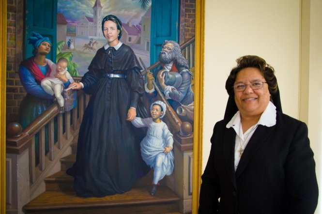 Sister Greta Jupiter, congregational leader of Sisters of the Holy Family of New Orleans, stands near a portrait of the founder of the order, Henriette Delille. Artist Ulrick Jean-Pierre created the piece, which was installed recently at the Motherhouse on Chef Menteur Highway.