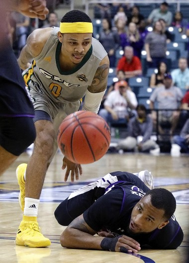Southeastern Louisiana guard Marlain Veal (0) scoops up the ball after Stephen F. Austin guard John Comeaux (10) loses the ball after falling during the second half of an NCAA college basketball game in the Southland Conference's Men's Basketball Tournament Championship Saturday, March 10, 2018, in Houston.