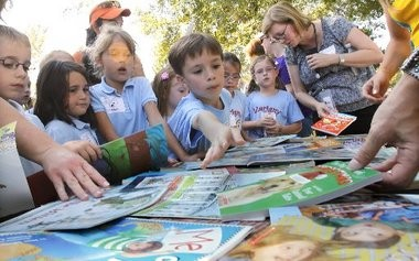 Elementary school students sort through books given away at the New Orleans Hornets recent bookmobile celebration. This Junior League of Greater Covington Jumpstart Read for the Record event was held at the site of future Children's Museum of St. Tammany, the Junior League's signature project.