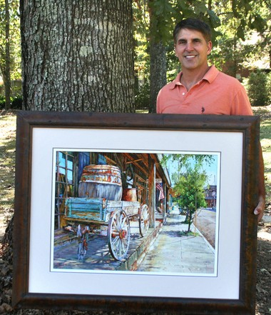 "Andry, seen here with the framed original of ""Wheels of Time,"" used H.J. Smith & Sons store as his inspiration for the watercolor painting. It will be available for purchase during the festival."
