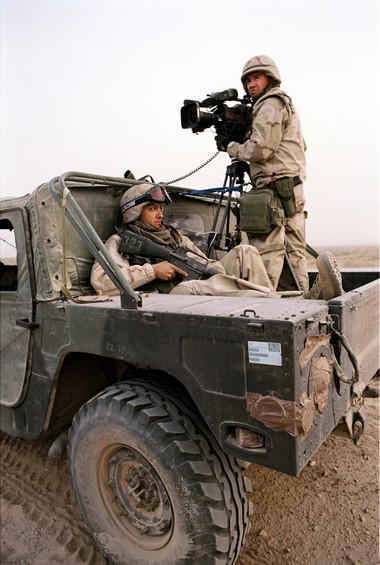 U.S. Marines cinematographer Sean Fairburn (pictured on right), shoots ground combat footage of Operation Iraqi Freedom. He is joined by Sgt. Carrillo (pictured on left), a combat illustrator. (Photo by US Marines Cpl Andy Revelos)