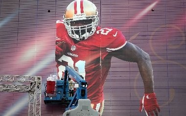 Workmen put up a giant image of San Francisco 49'ers running back Frank Gore on the side of the Superdome in advance of the Super Bowl on Thursday.