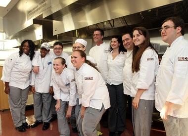 Chef Emeril Lagasse, third from right, and chef Frank Brigtsen, fifth from right, pose with NOCCA culinary students on March 22, 2011.