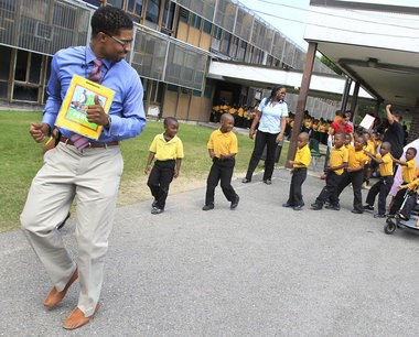 """Desmond Moore, then principal of Paul Habans Elementary, leads a """"parade of books"""" in May 2012."""