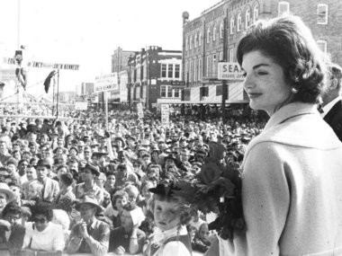 In mid October of 1959, Sen. John F. Kennedy and his wife Jacqueline visited Judge Edmund Reggie in Crowley, Reggie's hometown, attending the International Rice Festival, a parade and a dinner in Kennedy's honor. Jackie stands to the side as speeches are made. (Reggie Family Archives Photo)