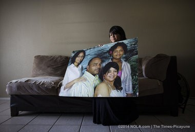 Kerry Washington's wife, Cheryl, holds onto a large portrait of the family back in happier times. Washington died on April 26, 2009 after being jailed at OPP, but his family did not find out for two weeks. His family was photographed at their home in Marrero on Friday, May 16, 2014. (Photo by Chris Granger, Nola.com | The Times-Picayune)