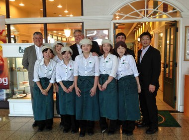 Cafe du Monde President Jay Roman, back row, second from the left, stands with employees at the Cafe du Monde Mizoguchi shop in Yokohama, Japan. The New Orleans cafe au lait and beignets stand has around 20 licensed franchises in Japan, the result of a business partnership cultivated after the 1984 world's fair. (Image courtesy of Cafe du Monde)