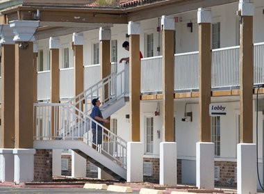 Workers mill about the Motel 6 on University Ave. Friday, July 24, 2015 where 59-year-old John Russell Houser stayed before shooting up the Grand Theatre in Lafayette.