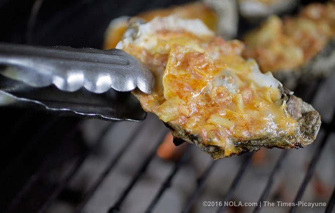 The proper method of removing oysters from the grill. (Photo by David Grunfeld, NOLA.com | The Times-Picayune)