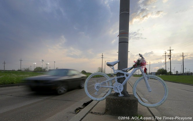A ghost bike is installed to memorialize the killing of cyclist Monique Massey late on the night of March 23, 2016 on Leon C. Simon Blvd. A car passes the Monique Massey ghost bike at high speed as twilight sets in. (Photo by G. Andrew Boyd, NOLA.com | The Times-Picayune)