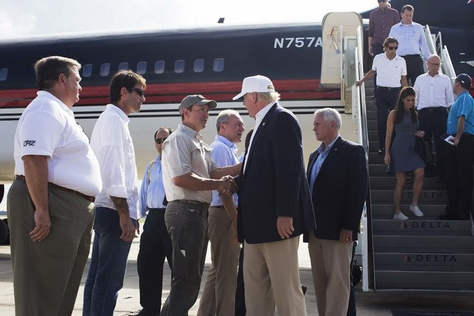 Republican presidential candidate Donald Trump, followed by his running mate, Indiana Gov. Mike Pence, shakes hands with Louisiana Attorney General Jeff Landry as he is greeted by Louisiana officials upon his arrival at the Baton Rouge airport Friday, Aug. 19, 2016. (AP Photo/Max Becherer)