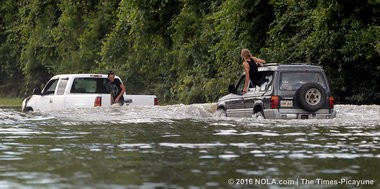 The Comite River covers Louisiana 946 as residents drive through the high water in Central, north of Baton Rouge, on Aug. 15, 2016. (David Grunfeld, NOLA.com | The Times-Picayune archive)