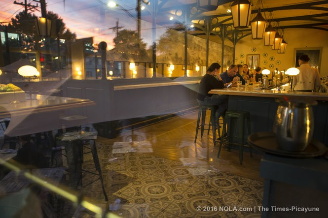 A sunset is reflected on a window as diners sit at the bar inside Kenton's. (Photo by Chris Granger, Nola.com | The Times-Picayune)