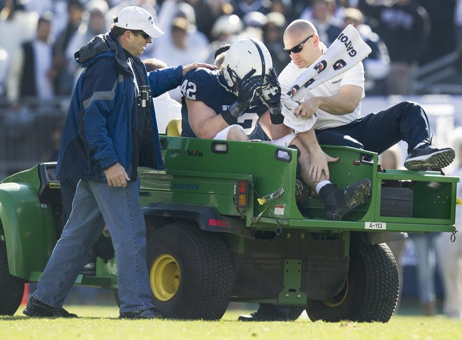 Penn State linebacker Michael Mauti is consoled by his father, Rich, after suffering a torn ACL in his left knee, prematurely ending his senior season. (Joe Hermitt, The Patriot-News)