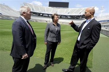 Penn State President Eric Barron, new athletic director Sandy Barbour and football coach James Franklin talk on the field of Beaver Stadium in State College, Pa. on Saturday, July 26, 2014. Barbour replaces David Joyner, who announced he was resigning last month. Joyner took over at Penn State in the wake of the Jerry Sandusky scandal and held the job for two and a half years.
