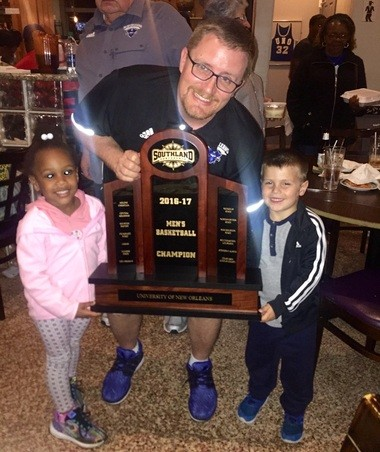 Mark Slessinger celebrates UNO's 2016-2017 Southland Conference regular-season title with daughter, Nola, left, and son Holden.