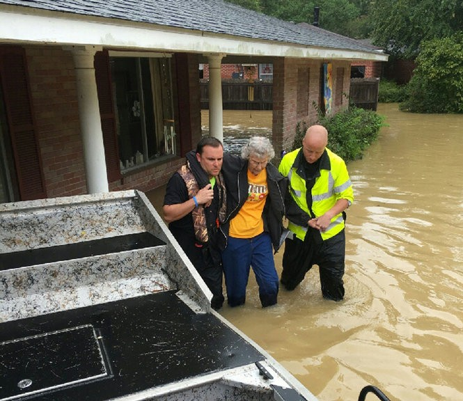 Plaquemines Parish Sheriff's Office Major Grant Solis, left, and another first responder help an elderly woman from her flooded home in Livingston Parish Saturday Aug. 13, 2016. (Photo courtesy Plaquemines Parish Sheriff's Office)