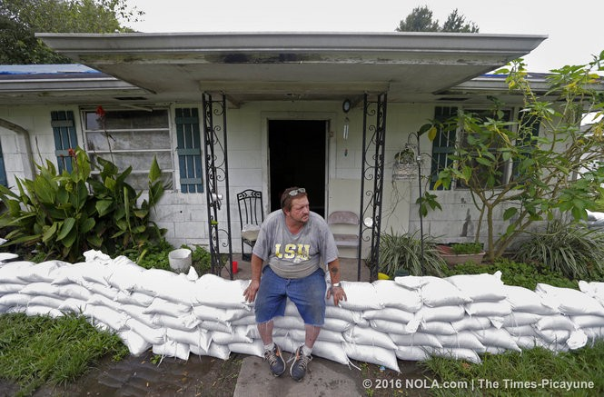 Carroll Webre sits on sandbags around his home in Gramercy on Tuesday, August 16, 2016. (Photo by Brett Duke, Nola.com | The Times-Picayune)