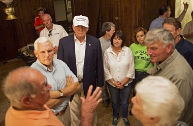 Republican presidential candidate Donald Trump, center, and his running mate, Indiana Gov. Mike Pence, listens to flood victims Jimmy and Olive Gordan during a tour of their flood damaged home in Denham Springs, La., Friday, Aug. 19, 2016. (AP Photo/Max Becherer)