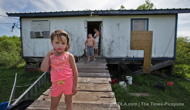 Amiya Brunet, 3, and her brother Ayden, 6, cross the boardwalk from their home on Isle de Jean Charles.