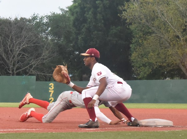Brother Martin first baseman Tre Morgan (12) waits for the throw as Rummel's Ron Franklin 23) dives back into the base.