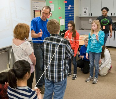 Intel volunteer engineer Ryan Warr gives suggestions to West Union Elementary students building an imaginary suspension bridge with help from classmates. The visit by Warr and parent Intel volunteer Keisha Thomas (in background) is part of the Hillsboro school's Smart Cart program, a rolling laboratory with simple science, technology, engineering and math (STEM) activities.