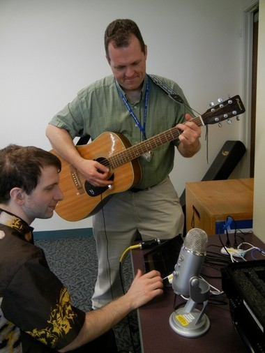 Rob Polivka (foreground), a reference assistant at the Cedar Mill Community Library, tries out one of the library's new Media Maker technology recording and editing kits while Mark Richardson, young-adult and reference librarian, provides music.