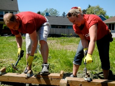 Keller Williams Sunset Corridor employees John Fogarty (left) and Amber Gilley work to salvage wood from a deck they helped demolish at the nonprofit Edwards Center's Aloha site.