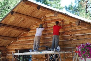 Volunteers Casey (left) and Jay Chitwood of Joseph buff and chink logs on the Divide Camp Lodge, a 50-year-old hunting camp in northeast Oregon being renovated as a haven for wounded American soldiers and sailors.