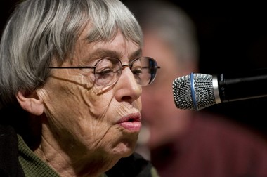 """Ursula K. LeGuin reads her book """"A Ride on the Red Mare's Back"""" during a rehearsal at Reed College with the Third Angle New Music Ensemble, five musicians who accompanied her while illustrations from her book are shown on a screen behind them."""