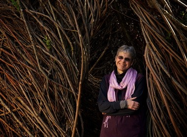 Author Mina Carson is shown inside a living sculpture of woven willows at People's Park on the OSU campus.