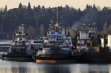 Three tugboats continue waiting Friday off the Willamette River's main channel in Portland, to be operated by non-union crews in case of a lockout or strike.