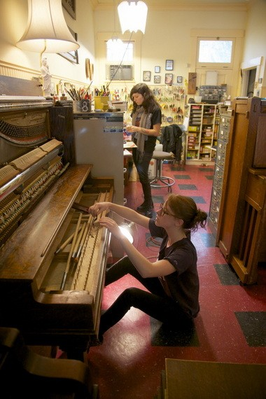 Immortal Piano Co. apprentices Marian Kidd, foreground, and Lauren Vidal work to rebuild vintage pianos, a task that can take more than 100 hours of labor. The southeast Portland business specializes in American uprights built before 1928, and sells about 100 a year.