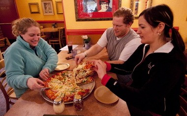 Customers, from left, Bri Voight, her husband, Jon Voight, and Gina Harrison divide a pie at Pietro'Âs Pizza in Milwaukie.