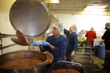 Better Bean Co. employee Santos Gutierrez strains beans before they are sauteed in safflower oil at the company's Wilsonville production plant.