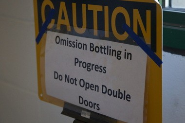 A sign between Craft Brew Alliance's grain handling area and packaging area warns workers at the Portland brewery when Omission beer is being bottled.