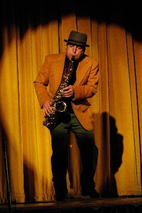 Shoehorn is an original performance artist who creates music with his feet and dances with his horn. Michael Shoehorn Conley has combined organic body rhythms and sophisticated jazz forms and concepts into an entertaining spectacle. While specializing in sax and tap dance, he is a multi-instrumentalist, arranger and composer, utilizing a variety of wind and percussion instruments, original poetry and songs and an ear for music from around the world.