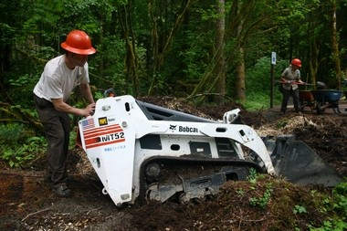 John Peterson with the Bureau of Land Management maneuvers a mini loader to pick up a pile of mulch at the new Three Bears recreation site on the Molalla River.