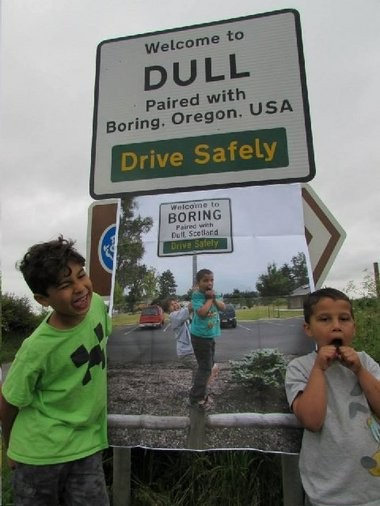 Kids in Dull, a village in Scotland, stand next to a sign announcing the community's partnership with Boring in Oregon. Oregon legislators made Aug. 9 the official Boring & Dull holiday.