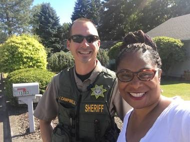 Oregon state Rep. Janelle Bynum takes a photo with a Clackamas County deputy who responded to a 911 call from one of her constituents who thought she looked suspicious as she was canvassing in a Clackamas neighborhood on July 3, 2018.