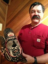 """Tsungani displays a shaman's mask he carved in July as part of his work at the Lelooska Foundation. Traditionally a Kwakiutl healer would use such a mask to promote a trance state in which he would receive supernatural healing powers. """"I enjoy a shaman's mask more than anything else,"""" Tsungani said. """"A shaman's art represents one individual's vision of the world."""""""