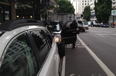 A motorists gets out of his parked car when the coast is clear in downtown Portland.