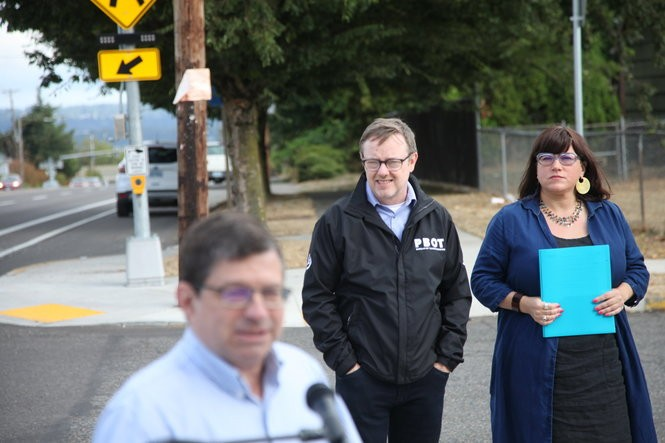 Former Commissioner Steve Novick (front), talks while his former chief of staff and the interim PBOT director, Chris Warner, and Commissioner Chloe Eudaly listen on at a Sept. 10, 2018 press conference on 122nd Ave.