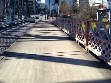 The afternoon sun on a recent day casts shadows on the Hawthorne Bridge. This view looks west and shows the sensor tubes that log the number of bikes that bump over them.