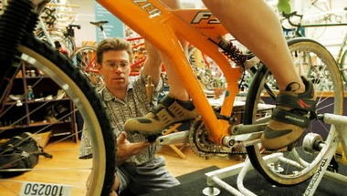 A Bike Gallery employee works on fitting a customer for a new bike at one of the Portland chain's stores. The retailer has made the bold move to not only honor the prices of its local competitors but also of online stores. Web stores often run with lower overhead and can offer cheaper products than brick-and-mortar stores.