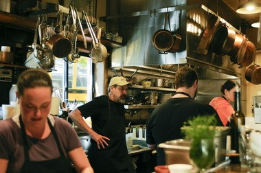 Greg Higgins (center) discusses the menu with sous chef Patrick Strong (back to camera). Higgins celebrates 20 years this year.