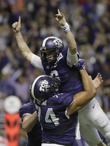 TCU quarterback Bram Kohlhausen is lifted by teammate Halapoulivaati Vaitai after throwing a touchdown pass in the first overtime in the Alamo Bowl against Oregon on Jan. 2.