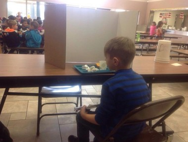 First-grader Hunter Cmela eats alone behind a screen as his punishment for being tardy more than four times this school year. His grandmother, Laura Lucas Hoover, was outraged and posted the image on Facebook.